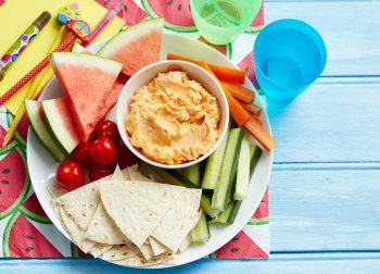 healthy childcare menu of wraps, dip, fruit & veg on a plate