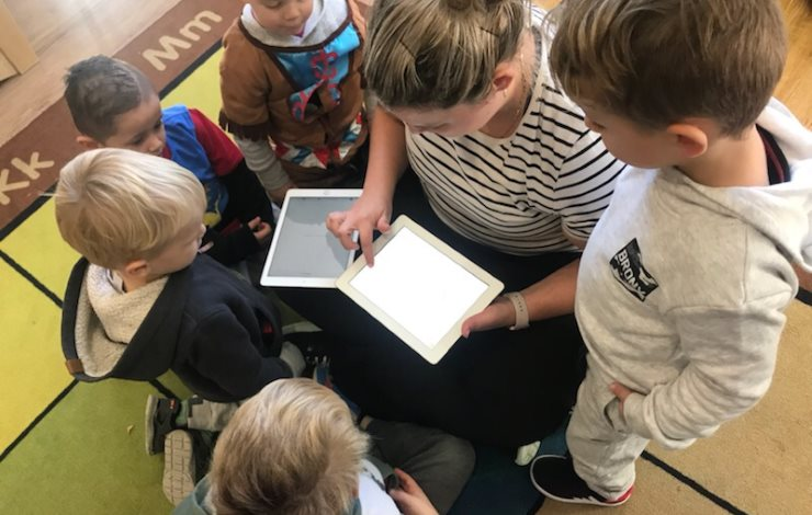 A child care worker shows children how to use an iPad