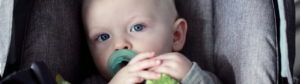 A young toddler with a pacifier sits in a baby seat