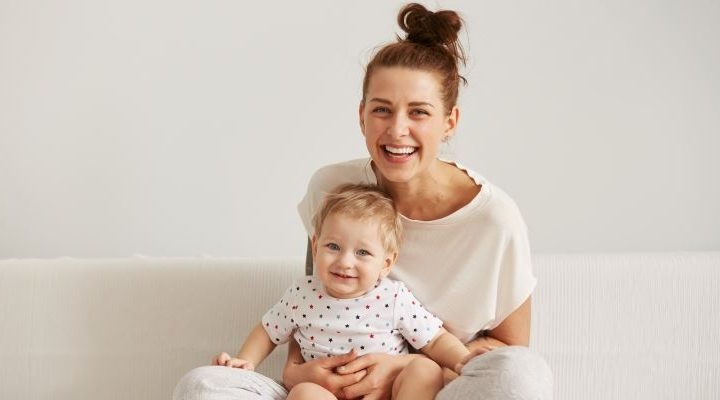 Happy smiling mother holding her child looking at camera