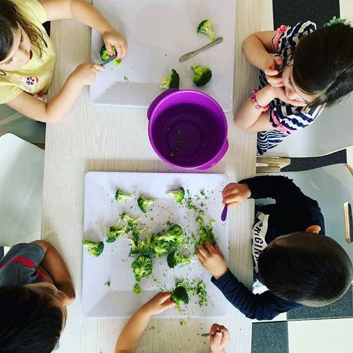 Preschoolers cutting up vegetables