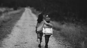 Big sister with her arm around her brother, walking down a gravel path