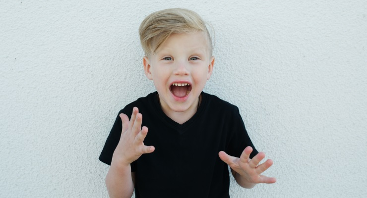 An excited boy standing against a white wall