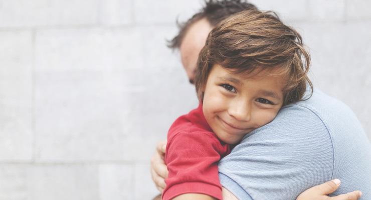 Preschool age child giving his parent a hug