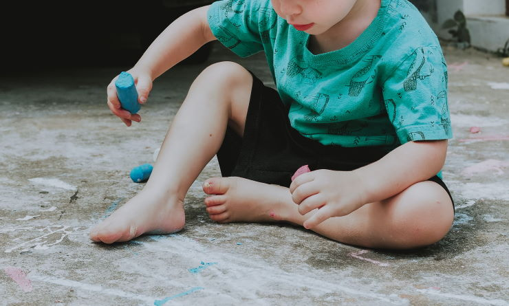 Young boy in a green shirt, black shorts and barefoot, sits on the floor playing with chalk