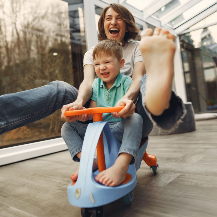 Mum and son going barefoot during playtime on a wheely cart