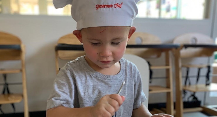Toddler playing chef in a kitchen at an early learning centre