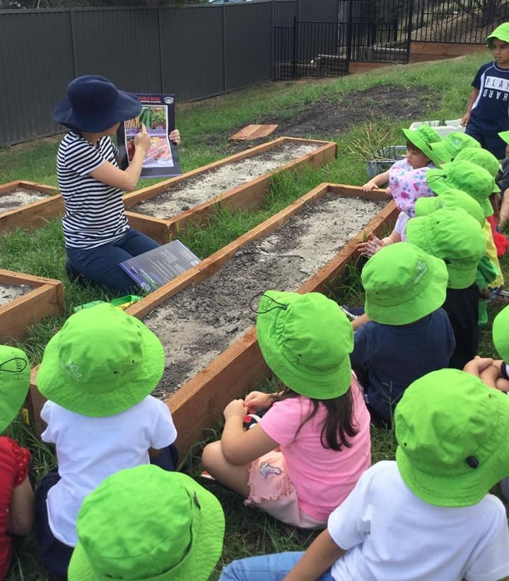A group of preschool children in green hats with a teacher in a vegetable patch