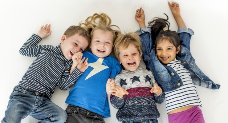 4 happy, laughing young children lying on the floor