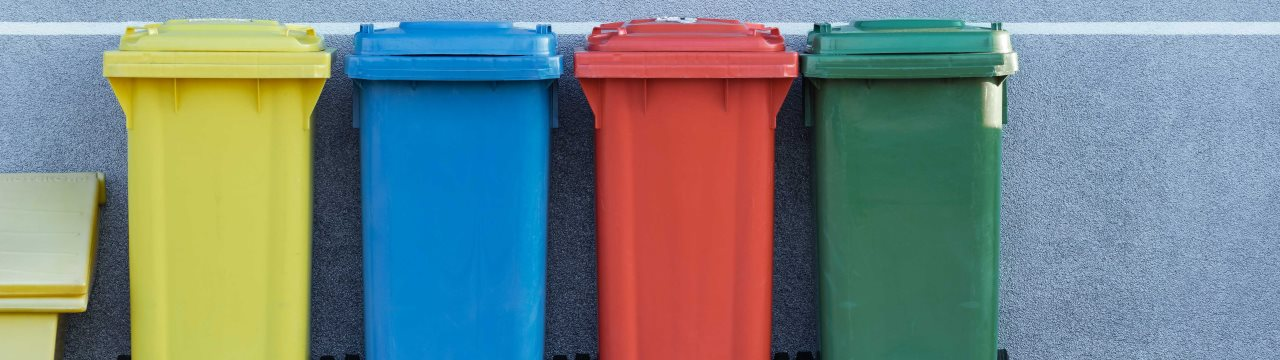 Four coloured bins in a row