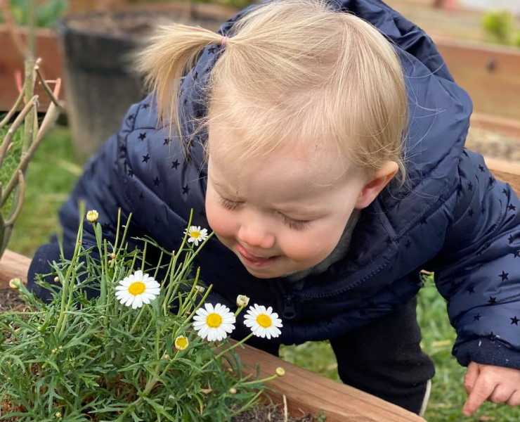 A young toddler smells the daisies, enjoying some outdoor play time