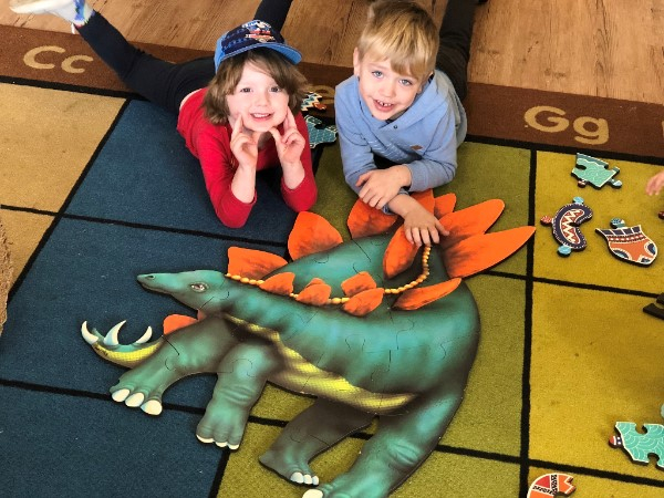 Two children at Grace Village show off their dinosaur puzzle