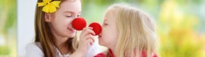 Two girls with red clown noses playing