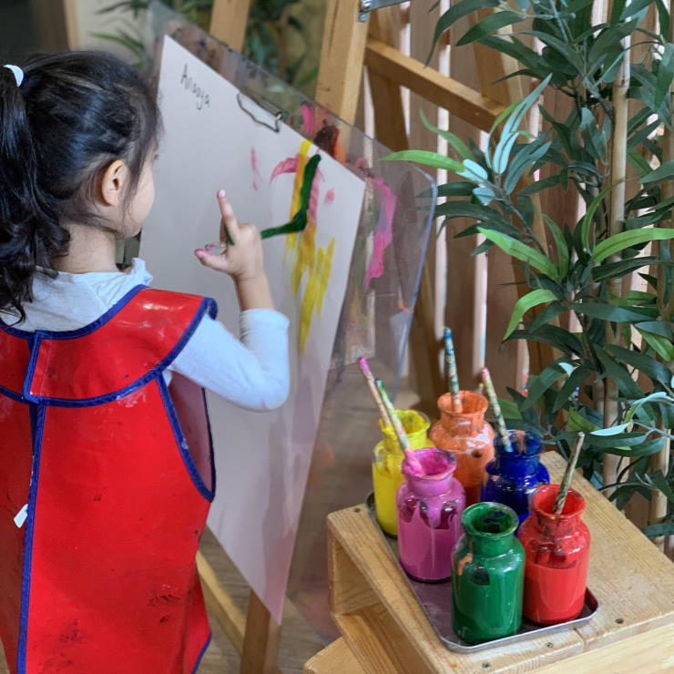A young child painting to develop fine motor skills as part of the school readiness program at Grace Village ELC