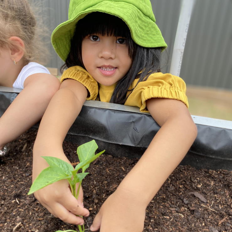 A young girl at Grace Village ELC plants a seedling