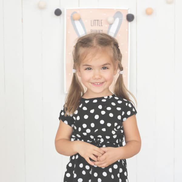 A young girl in polka dot dress smiles at the camera