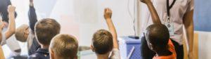 School children raising their hands in front of a teacher